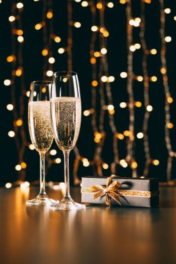 Glasses of champagne and present on garland light background, christmas concept stock vector