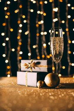 surface level of champagne in glass and gift boxes on garland light background, christmas concept