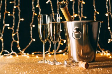 champagne bottle in bucket and two glasses on garland light background, christmas concept