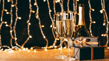 two glasses of champagne, presents and bottle on garland light background, christmas concept