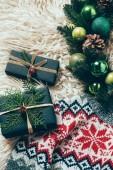 Draufsicht der verpackte Weihnachtsgeschenke, Weihnachten Kranz und Winter Pullover auf wollene Hintergrund