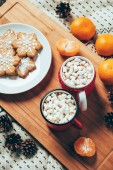 Photo top view of cups of hot chocolate with marshmallows, cookies and tangerines on blanket background, christmas breakfast concept