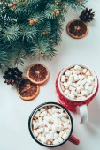 Photo top view of cups of hot chocolate with marshmallows and pine tree branches on white surface, christmas breakfast concept