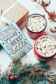 Photo top view of postcard with have yourself marry little christmas lettering, present and cups of cocoa drinks with marshmallows on white tabletop