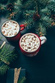 Photo top view of wrapped christmas presents and cups of hor chocolate with marshmallows on black tabletop