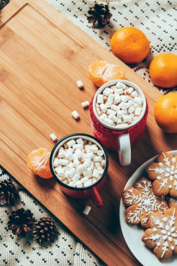 top view of cups of hot chocolate with marshmallows, cookies and tangerines on blanket background, christmas breakfast concept