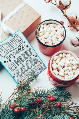 Top view of postcard with have yourself marry little christmas lettering, present and cups of cocoa drinks with marshmallows on white tabletop stock vector