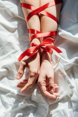cropped shot of male and female hands tied with red ribbon on bed
