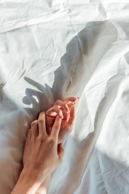 partial view of couple in live holding hads while lying in bed together