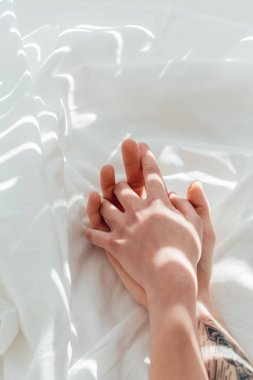 partial view of loving couple holding hands while lying on white bed sheet