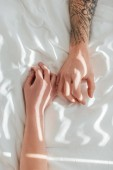 cropped shot of loving couple lying on white bed sheet together