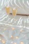 Fotografia Chiuda sulla vista di garland e bicchieri di champagne sul letto con lenzuolo cuscino e whire