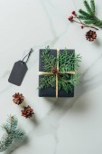 top view of black christmas gift box with fir branches and tag on marble table