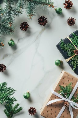 top view of christmas gift boxes with fir branches and pine cones on marble background with copy space
