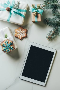 top view of christmas presents, snowflake cookies and digital tablet with blank screen on marble background