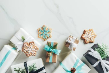 flat lay with christmas gift boxes and snowflake cookies on marble background with copy space