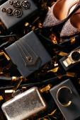 Fotografie plochý ležela s ženské boty, kabelku a šperky na černém pozadí s zlaté konfety