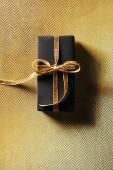 pohled shora zabalené dárkové krabičce se zlatou stuhou na zlaté pozadí