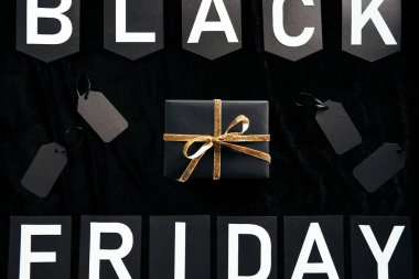 Top view of black friday lettering, wrapped gift and blank price tags on black backdrop stock vector
