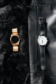 top view of luxury masculine and feminine wrist watches on black leather and woolen background
