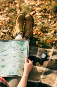person in pair of orange boots holding map on background of colorful foliage