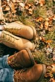 Draufsicht auf zwei Paar orangefarbene Stiefel im schönen Laub im Herbst