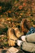 Ausgeschnittener Blick auf zwei Paar orangefarbene Stiefel im schönen Laub im Herbst