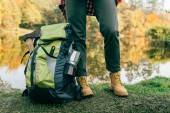 Photo cropped image of traveller legs with backpack on autumnal background