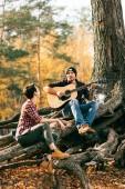 boldog nő és férfi birtoklás móka-val gitár, háttér autumal