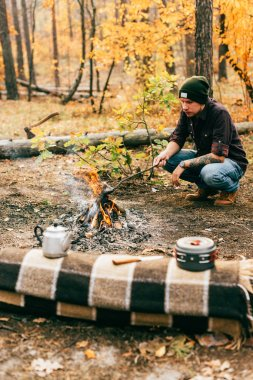adult man cooking food by fire outdoors in autumn forest