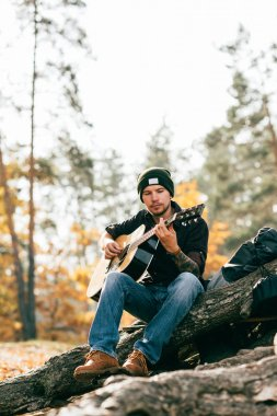 adult male playing acoustic guitar sitting on tree in park