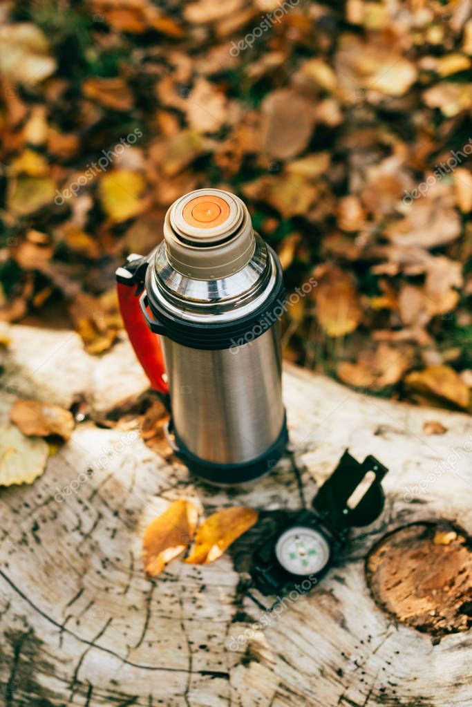 top view of metallic camping thermos on beautiful autumnal background