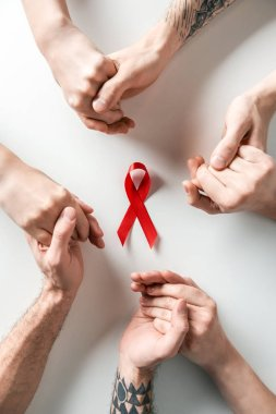 top view of people holding hands and aids awareness red ribbon on white background
