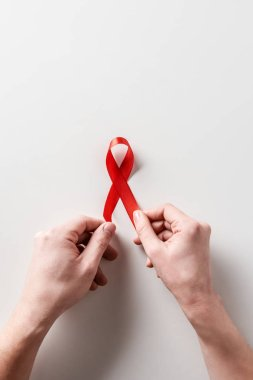 male hands holding aids awareness red ribbon on white background