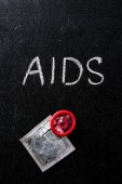 Fotografia vista superiore del preservativo rosso e segno di aids con imballaggio dargento su sfondo nero
