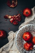 Photo food composition with ripe and fresh pomegranates, metal bowl and gauze on black tabletop