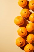 Top view of arranged fresh tangerines on beige background