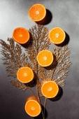Fotografie plochý ležela s půlky uspořádány mandarinky a zlatý proutek na šedém pozadí