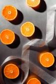 plochý ležela s půlky uspořádány mandarinek s stříbrná stuha na šedém pozadí
