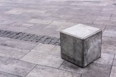 Photo close up view of grey stone cube at urban street