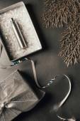 Fotografia vista superiore della bottiglia di profumo in confezione regalo, nastro dargento e decorativi lucidi ramoscelli su grey
