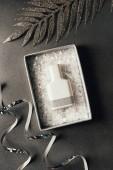 Fotografia vista superiore della bottiglia di profumo in nastri di casella, dargento e lucido decorativo foglie su grey