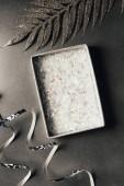 Fotografia vista superiore del contenitore di regalo aperto, nastri dargento e foglie lucide decorativi su grey