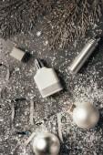 Fotografia vista superiore di profumi in bottiglia e bagattelle di Natale splendente sul grigio