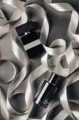 Fotografia vista superiore di bottiglie di profumi e nastri bianchi su grey
