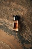 Draufsicht auf eine Flasche Parfüm auf braun verwitterter Oberfläche