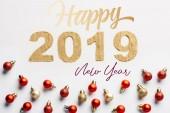 pohled shora 2019 rok zlaté znamení a vánoční koule na bílém pozadí s nápisem happy new year