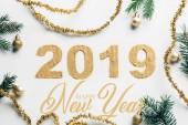 Fotografie pohled shora na rok 2019 znamení, borové větve, zlaté věnce a vánoční koule na bílém pozadí s nápisem happy new year