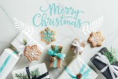 Fotografie flat lay with christmas gift boxes and snowflake cookies on marble background with merry christmas lettering