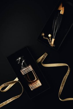 top view of perfume bottle with golden ribbon, gift box and decorative feathers on black